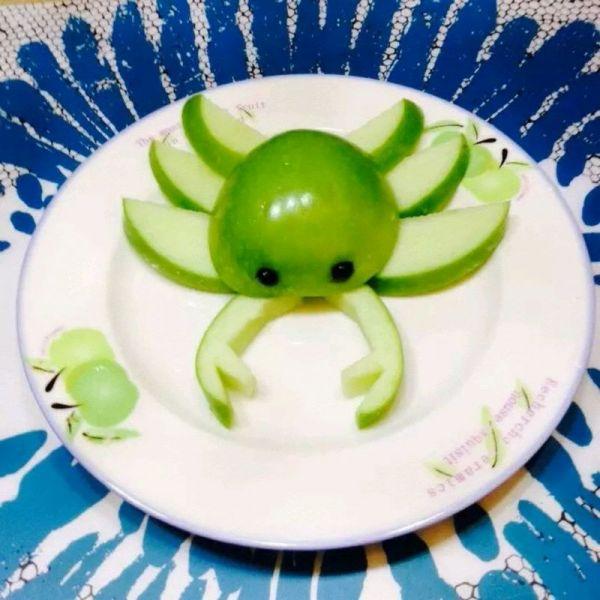 1.选一只青苹果(红色的也可以,这只刚好和盘子颜色一样),洗净,蓝莓两颗 2,将苹果一分二剖开,去中间核和籽,一半当小螃蟹身体,用小刀刻两个小洞将蓝莓放进去做眼睛,另一半切成四份薄片,其中三份再对切,最后一份用小刀刻出蟹钳的样子。 3,如图摆放就成功了。