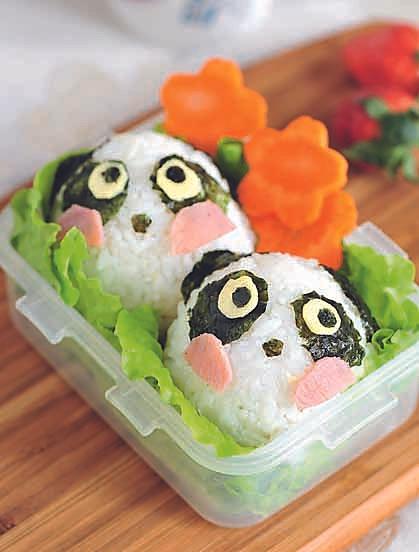 将寿司米饭放在手心平铺,放入儿童肉松,捏成椭圆的熊猫身形图片