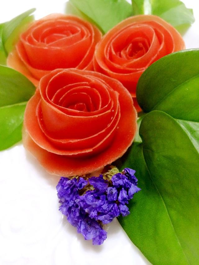 1. 1、三个新鲜、个头均匀的番茄,洗干净后用水果刀或者削皮器像削苹果一样把番茄皮削下来,皮不要弄断。2、把番茄的外皮向内卷起来,尽量卷的紧一些。3、把卷好的番茄皮的卷倒扣在盘子上,用蔬菜或者植物的绿叶做点缀,漂亮的番茄玫瑰花就做好了。