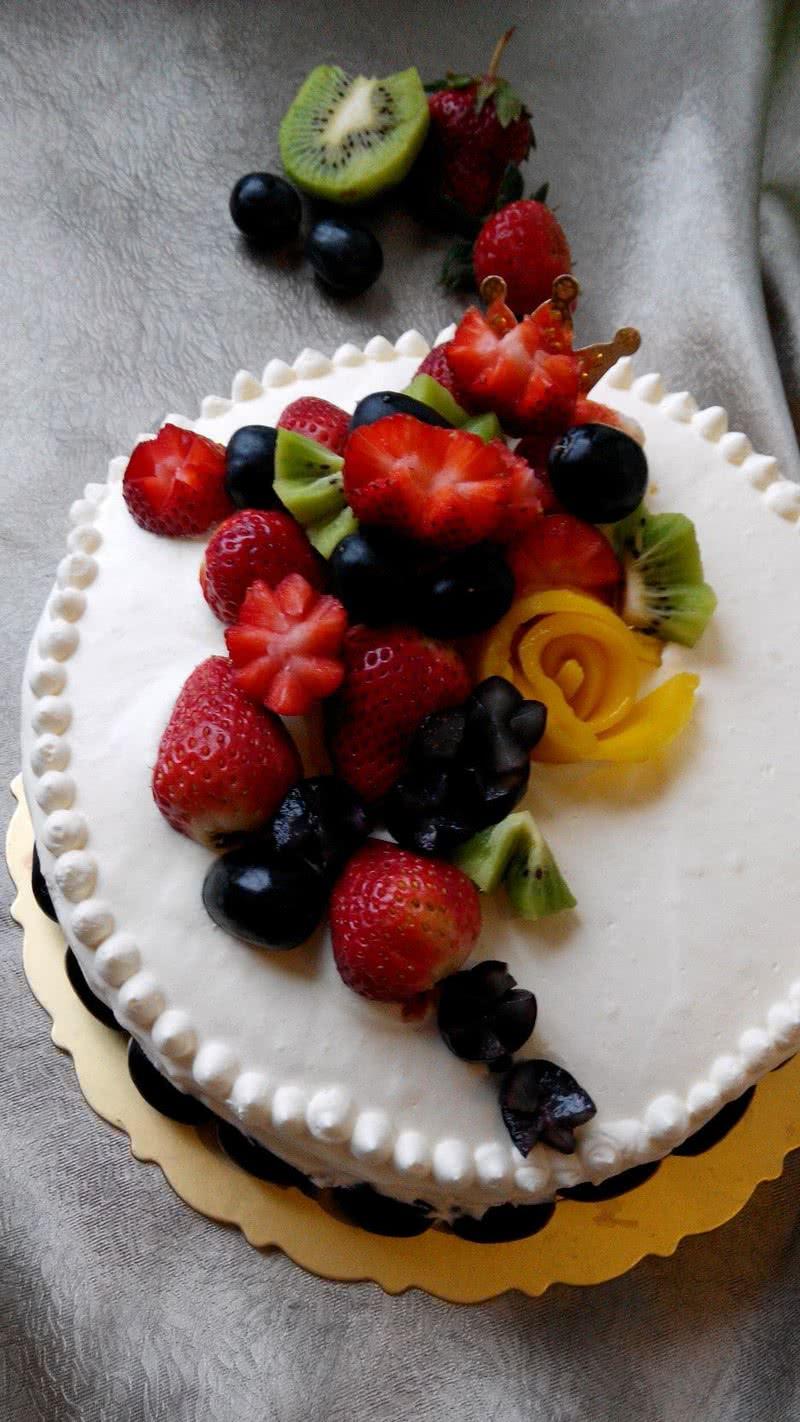 7. 将第一片蛋糕放在底部,倒入多一些的奶油放入中部,用抹刀45度角往下压并转动裱花台抹平后放入水果粒,再放第二片蛋糕,同样方法最后放入第三片蛋糕,抹表面一定要舍得放奶油以免蛋糕末混入奶油且不易抹平,再填一些奶油在侧面抹刀垂直于裱花台,转动裱花台让侧面的奶油抹平,最后用齿形抹刀抹出侧面的条纹,